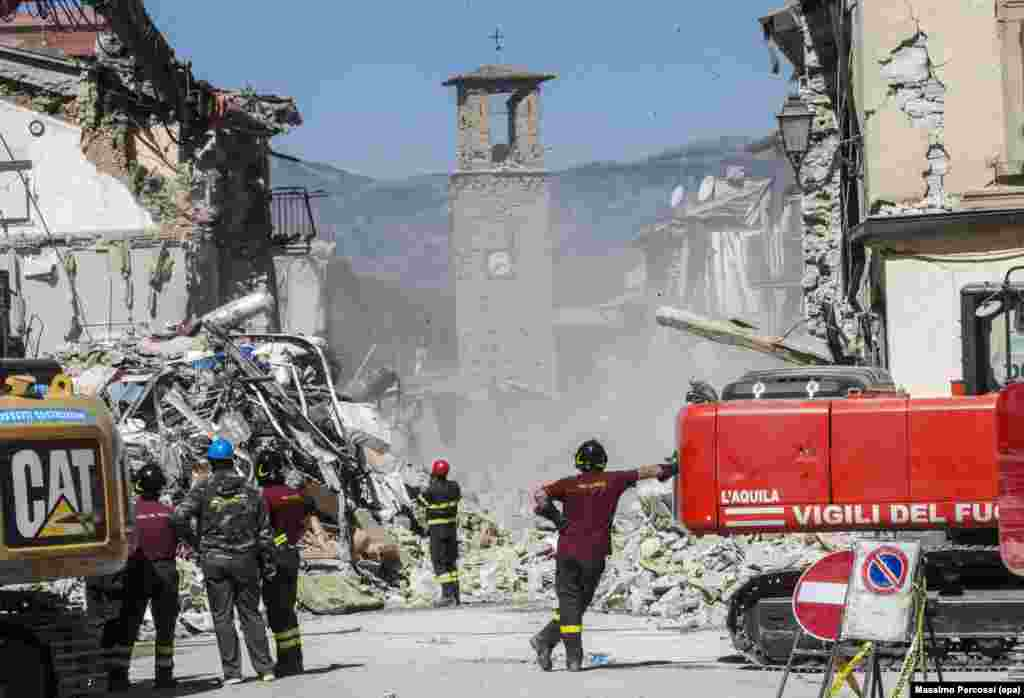 Members of the Italian Fire Brigades operate near the still-standing Civic Tower in the earthquake-stricken town of Amatrice. The latest provisional death toll from the August 24 earthquake is 290. (epa/Massimo Percossi)