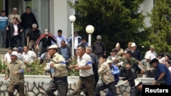 Supporters of the interim government assault the administration headquarters in Osh after it was seized by backers of ousted president on May 14.