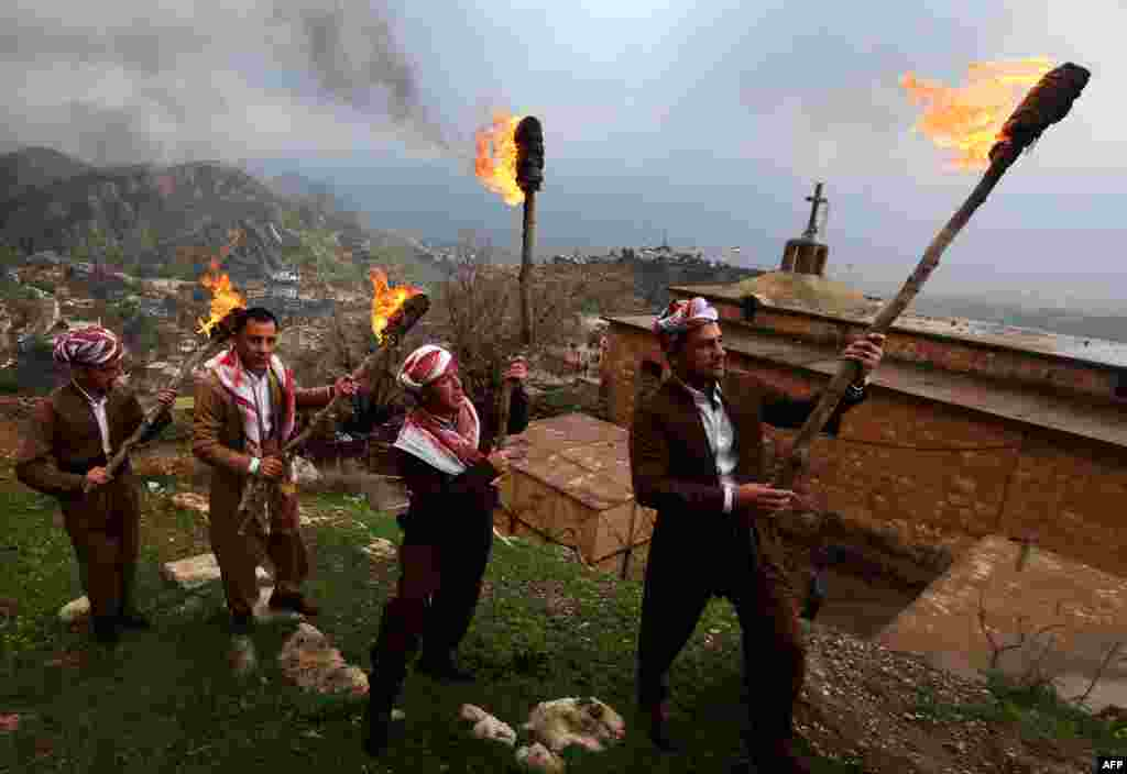 Iraqi Kurds holding lit torches walk up a mountain in the town of Akra, 500 kilometers north of Baghdad, as they celebrate the Norouz spring festival. (AFP/Safin Hamed)