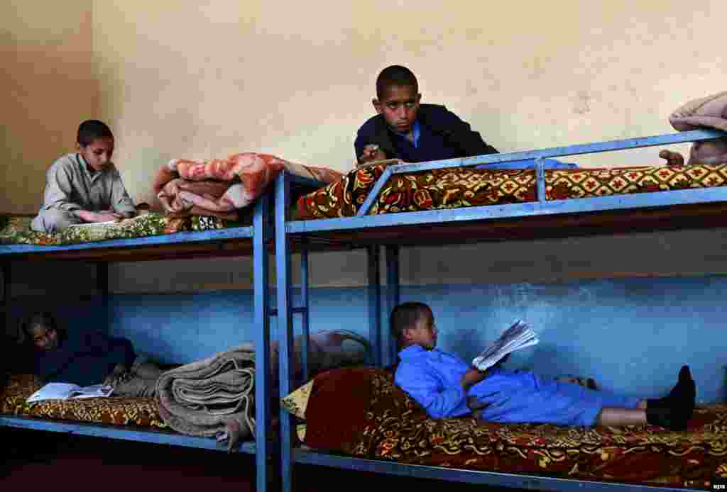 Afghan orphan children who lost their fathers to war, read books as they sit in their bunk beds at the Al-Nadwa orphanage in Jalalabad. (epa/Ghulamullah Habibi)