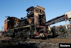 Шахтарі йдуть повз зруйнований поїзд на вугільній шахті «Комунарська № 22» у селі Нижня Кринка. 6 листопада 2014 року