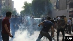 Protesters battle tear gas fired by police during a rally in Tehran on July 9.