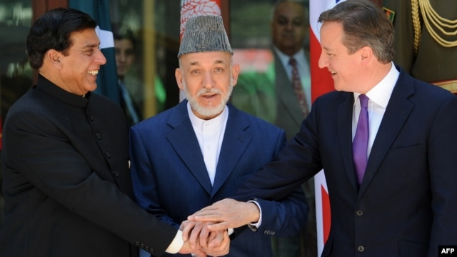 Afghan President Hamid Karzai (center), Pakistani Prime Minister Raja Pervez Ashfraf (left), and British Prime Minister David Cameron shake hands before a meeting at the Presidential Palace in Kabul on July 19.