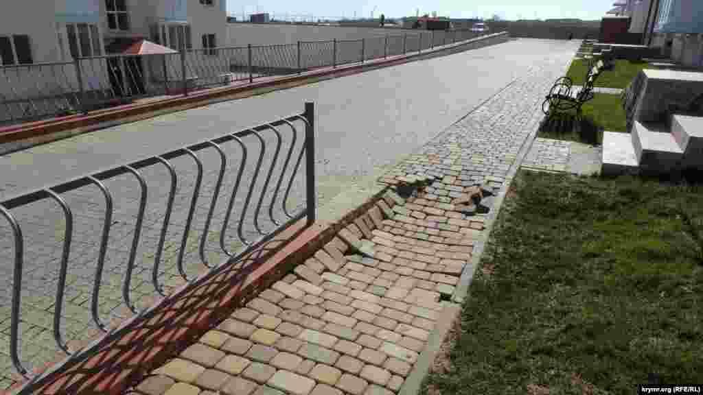 Через просідання ґрунту у дворі будинку почали руйнуватися викладені плиткою пішохідні доріжки