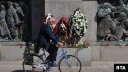 Възрастен мъж с маска минава пред паметника на съветската армия в Бургас