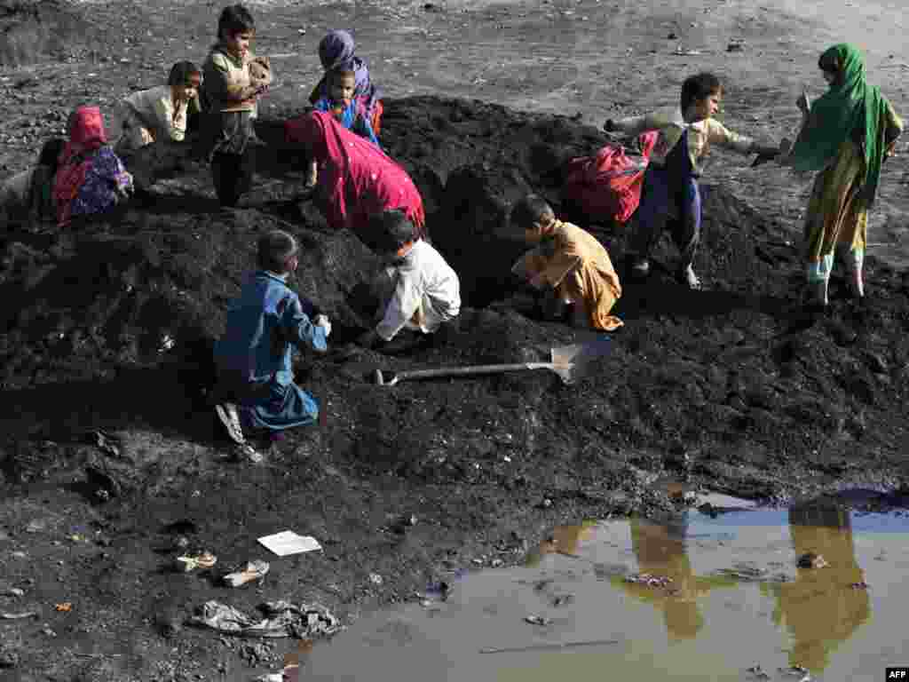 Children search for iron in waste sand in an industrial area of the Pakistani city of Islamabad.