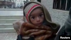 A toddler is held up to the camera in this still image taken from a video said to have been shot in Madaya on January 5.