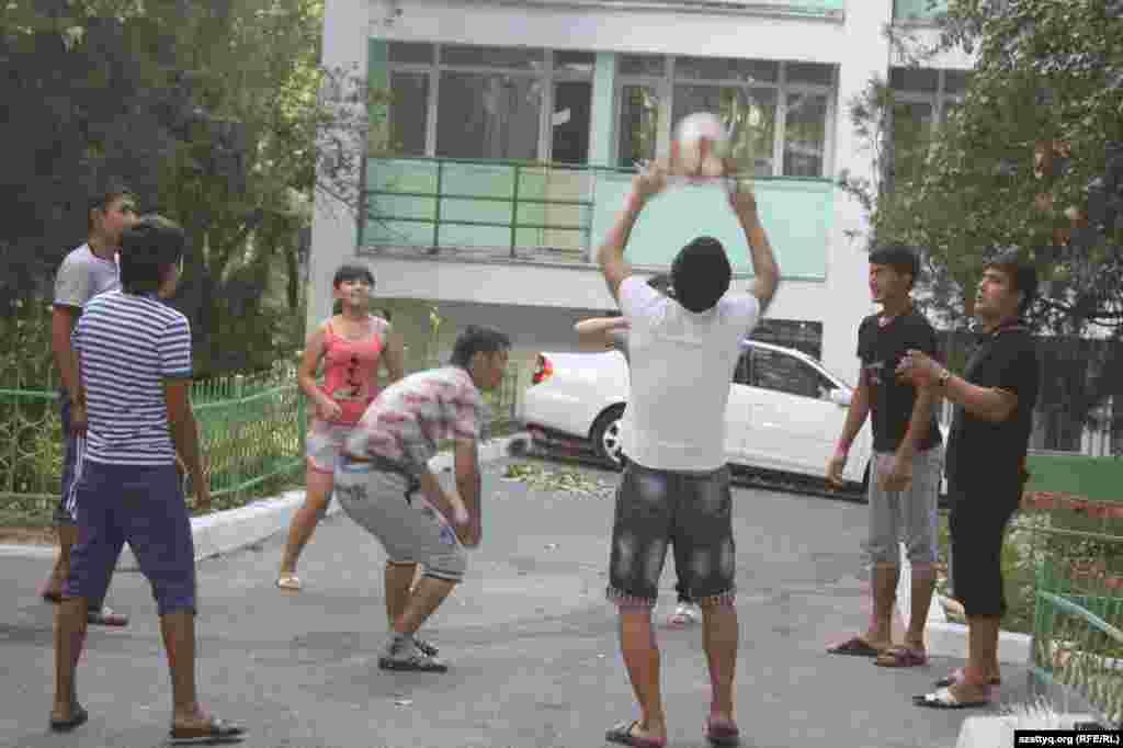 После занятий студенты играют с мячом во дворе общежития.