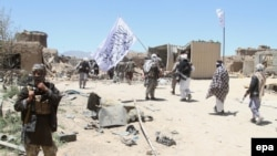 FILE: Suspected Taliban militants patrol after they reportedly took control of Ghazni's Waghaz district in May 2017.