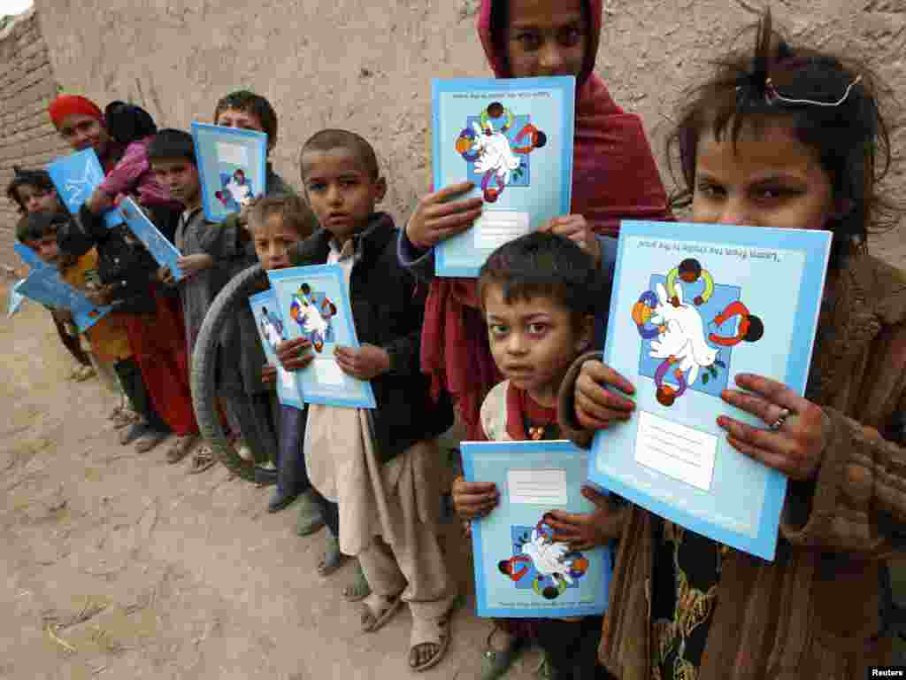 Afghan children hold exercise books distributed by Belgian Army soldiers during a joint mission with German Bundeswehr soldiers in the city of Iman Sahib, north of Konduz, northern Afghanistan, on December 15. Photo by Fabrizio Bensch for Reuters