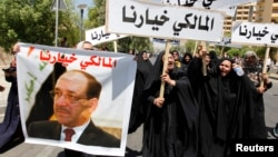 Iraqis hold posters of outgoing Prime Minister Nuri al-Maliki in support of him in Baghdad.