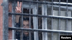 Belarus -- A detainee arrested in protests gestures from a prison cell at a detention center in Minsk, 29Dec2010.