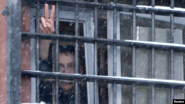 Belarus -- A detainee arrested in protests after the December election gestures from a prison cell at a detention center in Minsk, 29Dec2010