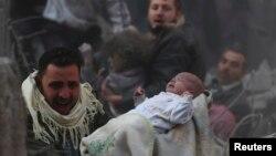 Выжившего ребёнка выносят из разрушенного при авиаударе дома в предместьях Дамаска, 7 января 2014 г.