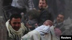 Выжившего ребёнка выносят из разрушенного при авиаударе дома в предместьях Дамаска. 7 января 2014 года.