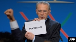 "IOC President Jacques Rogge shows the card reading ""Tokyo"" as he announces the winner of the bid to host the 2020 Summer Olympic Games."