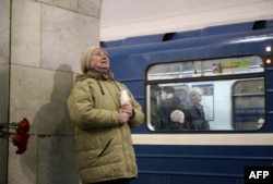 A woman reacts while placing flowers in honor of the victims of the April 3 blast on the platform of the Technological Institute subway station in St. Petersburg on April 4.