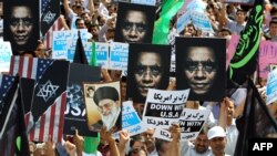 Iran -- Protestors hold anti-US posters as they demonstrate after Friday prayers against a film mocking Islam, in Tehran, 14Sep2012