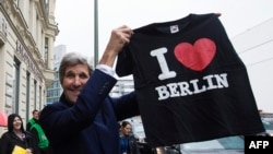 Գերմանիա - ԱՄՆ-ի պետքարտուղար Ջոն Քերրին Բեռլինը նախկինում արևելյան և արևմտյան մասերի բաժանող «Չարլի» անցակետի մոտ հուշանվերների կրպակում գնել է «Ես սիրում եմ Բեռլինը» շապիկը, 22-ը հոկտեմբերի, 2014թ.