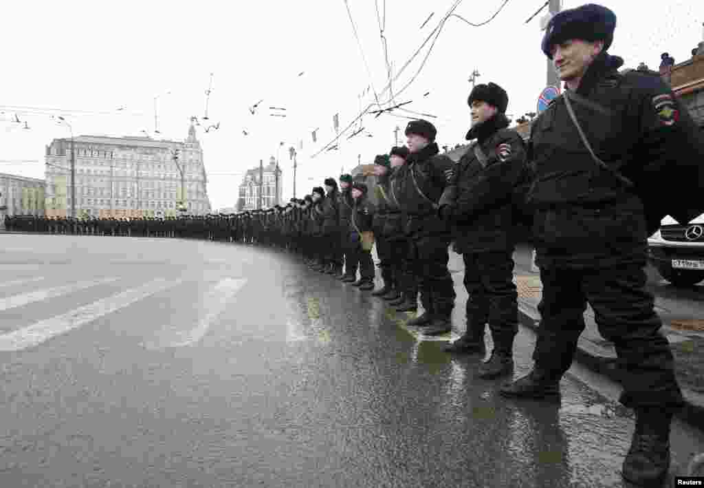 Riot police stand guard during the march to commemorate Nemtsov.