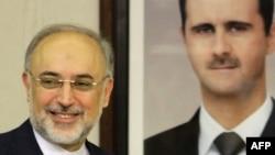 علیاکبر صالحی٬ وزیر خارجه ایران با تصویری از بشار اسد٬ رئیسجمهوری سوریه.
