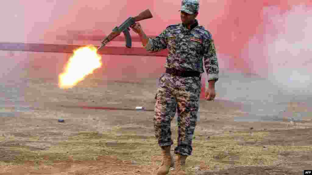 A police cadet fires his weapon during a graduation ceremony in Baghdad. (AFP/Ahmad al-Rubaye)