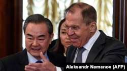 Russian Foreign Minister Sergei Lavrov (right) shows the way to Chinese counterpart Wang Yi during a meeting in Moscow on April 5.