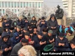 Тәуелсіздік ескерткіші алдында құран оқып отырған адамдар. Алматы, 16 желтоқсан 2019 жыл.