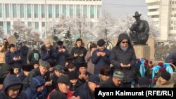 Собравшиеся у монумента Независимости на площади Республики читают молитву в память о погибших при трагических событиях в городе Жанаозене в 2011 году и выступлениях молодежи в декабре 1986 года. Алматы, 16 декабря 2019 года.