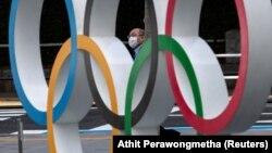 شهروند ژاپنی در حالیکه ماسک بر صورت زده در کنار نشان المپیک در نزدیک موزه المپیک ژاپن در توکیو رد میشود؛ ۱۳ مارس