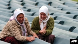 Muslim women weep over a relative's coffin at the Potocari memorial center near Srebrenica in July 2009.