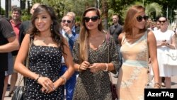"""Leyla (left) and Arzu (center) Aliyeva at the opening in Baku of an """"Azerbaijan in Cannes"""" cultural event. (file photo)"""