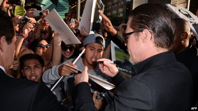 "Actor Brad Pitt (right) signs autographs as he attends the world premiere of Disney's ""Maleficent"" at the El Capitan Theatre in Hollywood on May 28."