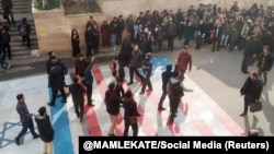 Several people walk on U.S. and Israeli flags while many others avoid stepping on the flags by walking around them, at the Shahid Beheshti University in Tehran, January 12, 2020