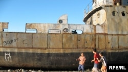Kazakh children play on an abandoned ship in the dry bed of the Aral Sea.