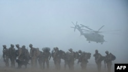 U.S. marines wait for helicopter transport in Helmand Province, a key site in the fight against Taliban militants.