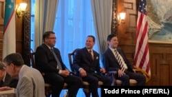 Uzbek Justice Minister Ruslanbek Davletov (left) and Capital Markets Development Agency Director Atabek Nazirov (right) speak to Baker McKenzie partner Thomas Firestone at the Uzbek Embassy in Washington on July 18.