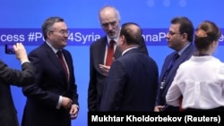 Syrian UN ambassador Bashar al-Jaafari (center) speaks with other participants during a session of the peace talks on Syria in Nur-Sultan in April.