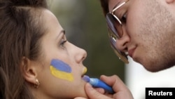 A man paints the colours of the Ukrainian national flag on a woman's face at the Euro 2012 fan zone in Kharkiv.