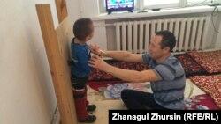 Асылбек Оспанов с сыном Рахатом, которому поставили диагноз ДЦП. Актобе, 11 декабря 2017 года.