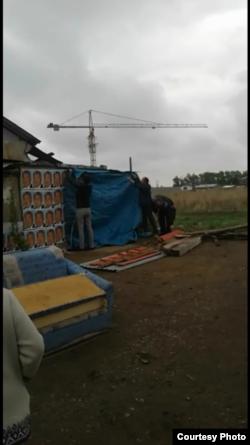 Рабочие и представители городского акимата срывают портреты президента Нурсултана Назарбаева с дачного дома жительницы Астаны Раушан Уябаевой. 13 мая 2017 года. Фото предоставлено Лесбеком Уябаевым.