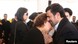 Ahmadinejad shihet duke i mbajtur duart Elena Friasit, nënës së Chavezit.