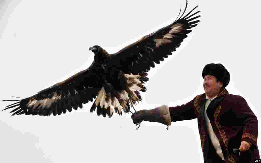 A Kyrgyz hunter flies a golden eagle during a hunting festival in the village of Cholpon-Ata.