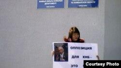 """Даметкен Жарылкасынова, руководитель филиала партии """"Алга"""" по Жамбылской области, проводит пикет у здания ДКНБ. Тараз, 15 марта 2012 года."""