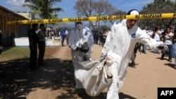 Крыміналісты выносяць цела згарэлага вязьня зь месца пажару ў турме Камаягуа, Гандурас. 15 лютага, 2012