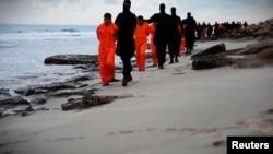 """«Крест еліне қанмен жазылған жолдау» деп аталған видеодағы """"ИМ содырлары"""" """"египеттік христиандарды"""" (қызғылт-сары киім киген) басын алуға әкеле жатыр."""