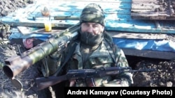 Andrei Kamayev poses with an antitank missile launcher and a Kalashnikov rifle in a trench in eastern Ukraine in January 2015.
