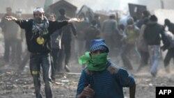 Протестующие бегут от полиции по одной из улиц, прилегающих к площади Тахрир
