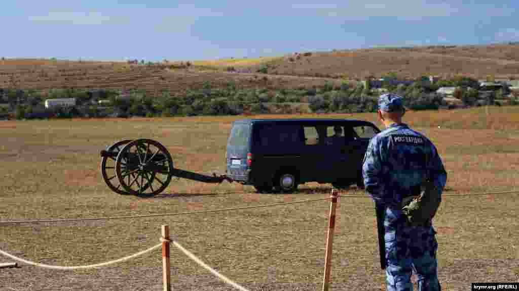 Современный боец Росгвардии в оцеплении наблюдает, как на позицию перемещают пушку времен Крымской войны 1853-1856 годов