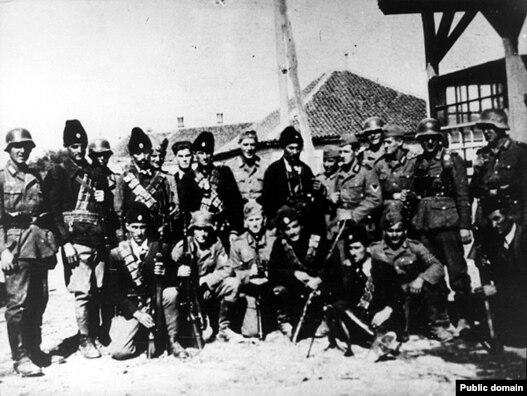 Grupa četnika pozira sa njemačkim vojnicima u selu u Srbiji, 1941-1945